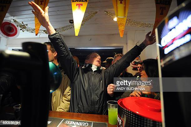 Celtic fans chant as they drink in a pub close to Celtic Park in Glasgow on December 17 2016 before the Scottish Premiership football match between...