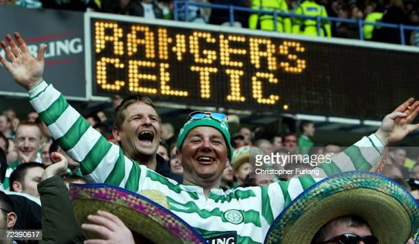 Celtic fans cheer on their team during the Scottish premier league match between Rangers and Celtic at Ibrox Stadium on March 28 2004 in Glasgow...