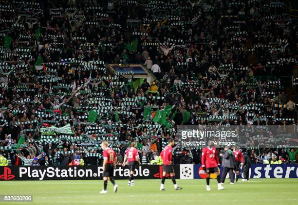 Celtic fans hold aloft scarves as Manchester United players look on