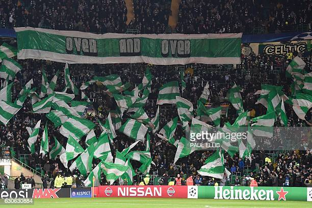 Celtic fans hold up team flags in the stands during the UEFA Champions League group stage football match between Celtic and Barcelona at Celtic Park...