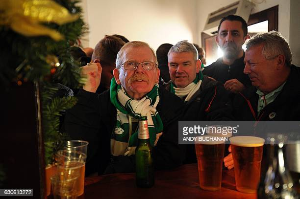 Celtic fans react as they drink in a pub close to Celtic Park in Glasgow on December 17 2016 before the Scottish Premiership football match between...