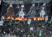 Celtic fans unveil a banner depicting their version of the four horsemen of the apocalypse during the Clydesdale Bank Premier League match between...
