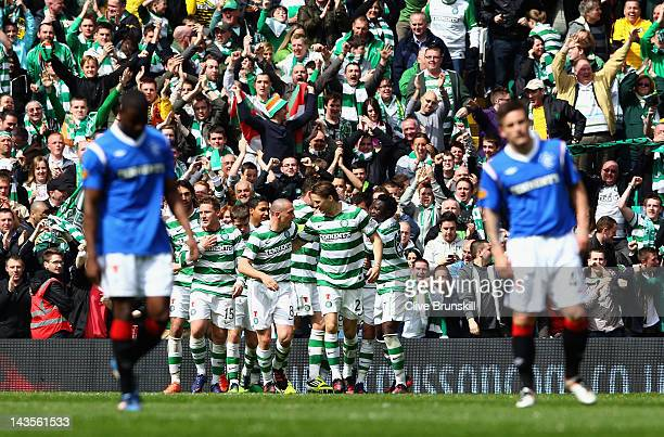 Celtic players celebrate Gary Hooper's third goal as Rangers players show their dejection in the forground in action with of Rangers during the...