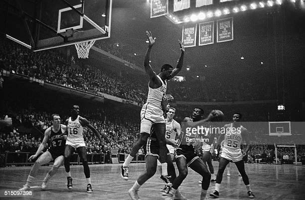 Celtics' Bill Russell makes a formidable appearance as guard against Royals' Oscar Robertson's attempt to score during the second quarter action in...