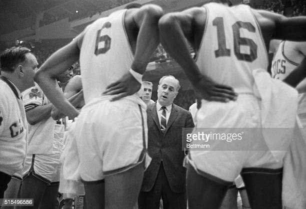 Celtics' coach Red Auerbach is dwarfed by his charges as he talks to them during timeout 4th quarter 1st game NBA Eastern Division Final Playoffs...