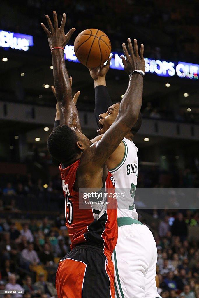 Celtics forward Jared Sullinger (#7) scored against Raptors forward Amir Johnson (#15) in the first quarter. The Boston Celtics play the Toronto Raptors in the Celtics' first NBA preseason game at TD Garden in Boston, Monday, Oct. 7, 2013.