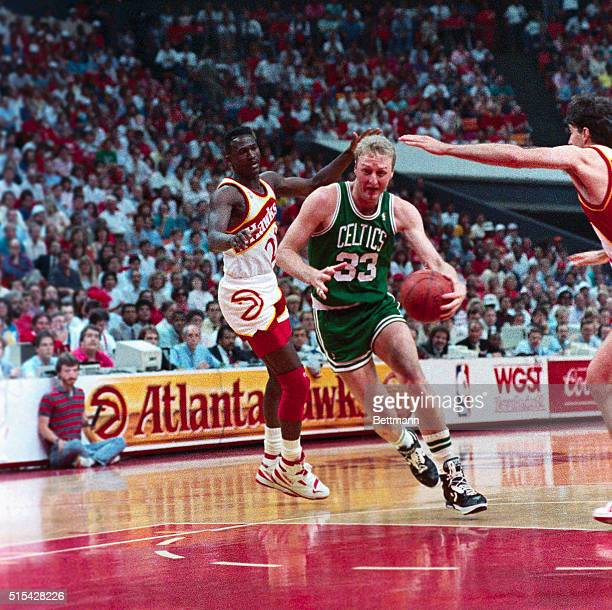 Celtics' forward Larry Bird goes to the basket over Hawks center Tree Rollins for two points during second period action here 5/20