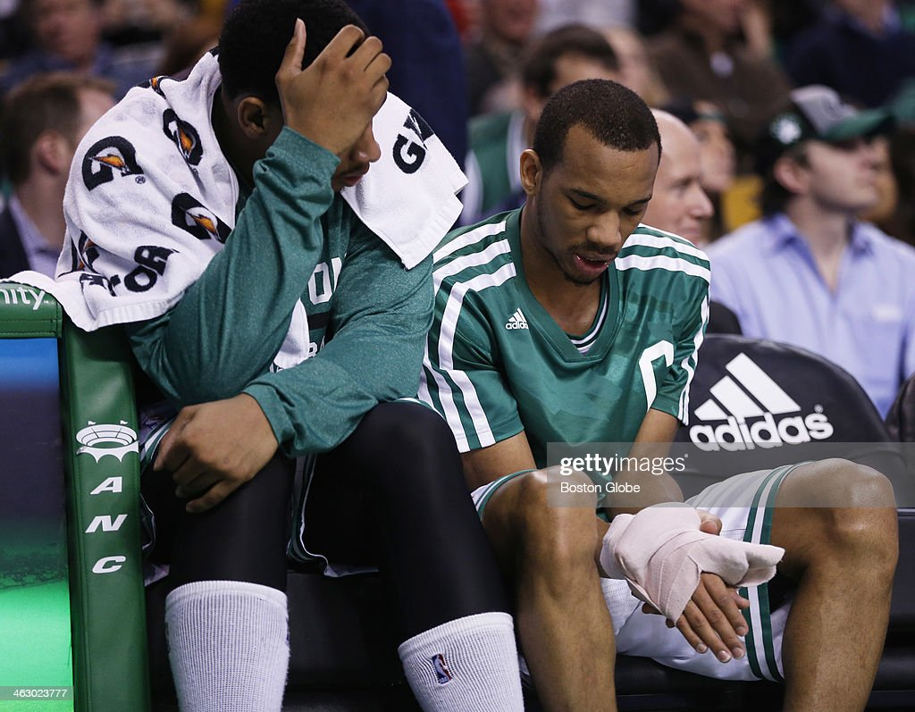 Celtics guard Avery Bradley (#0) looked at a bandaged hand with forward Jared Sullinger (#7) on the bench. Bradley would continue playing the game. The Boston Celtics played the Toronto Raptors at the TD Garden during a regular season NBA game in Boston, on Wednesday, Jan. 15, 2014.