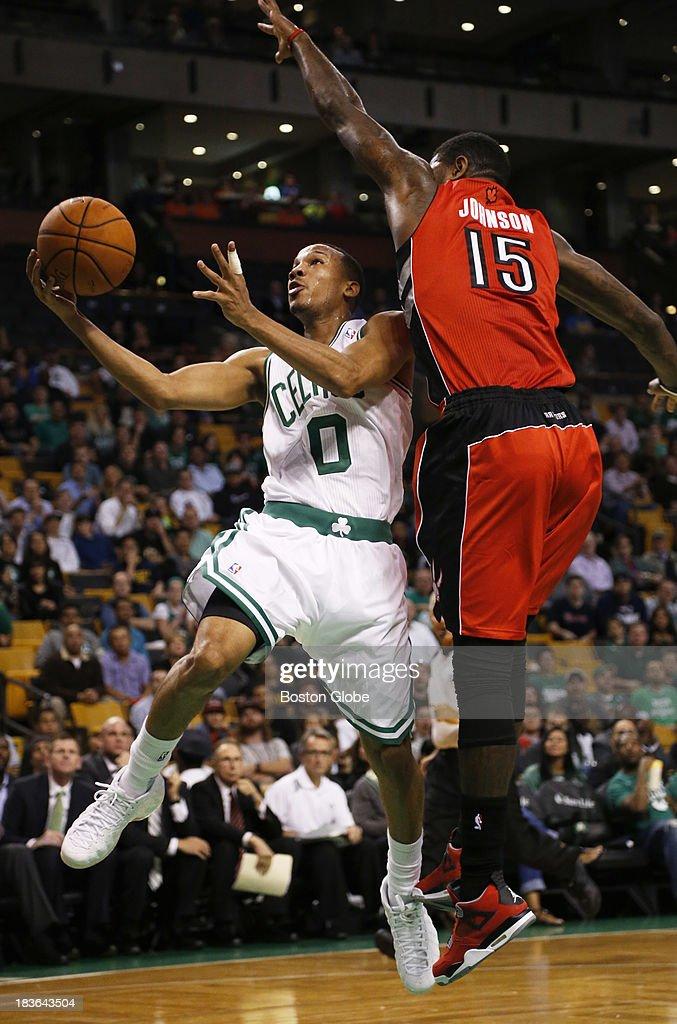 Celtics guard Avery Bradley (#0) scored a fast break layup against Raptors forward Amir Johnson (#15) in the first quarter. The Boston Celtics play the Toronto Raptors in the Celtics' first NBA preseason game at TD Garden in Boston, Monday, Oct. 7, 2013.