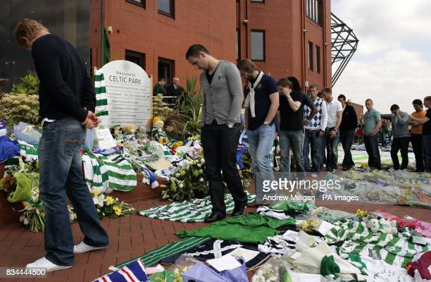 Celtic's John Kennedy looks at flowers after tributes are left for Tommy Burns at Celtic Park Glasgow