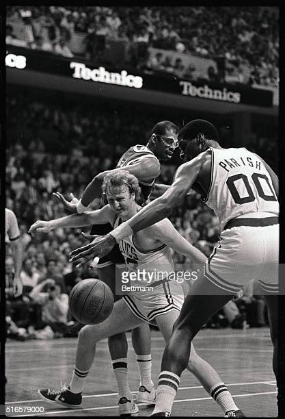 Celtics' Larry Bird finds the going rough as he falls while battling for a loose ball between Lakers' Kareem Abdul Jabbar and Celtics' Robert Parish...