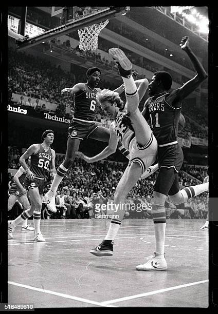 Celtics' Larry Bird trying to score does a high leg split as he is hit by 76ers' Caldwell Jones in 1st quarter action of the first game of the NBA...