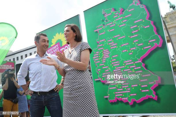 Cem Oezdemir and Katrin GoeringEckardt lead candidates of the German Greens Party stand in front of a map of Germany showing their upcoming election...