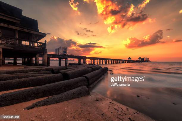 Cement bridge at the sea and the under construction pagoda with sunrise sunset low tides
