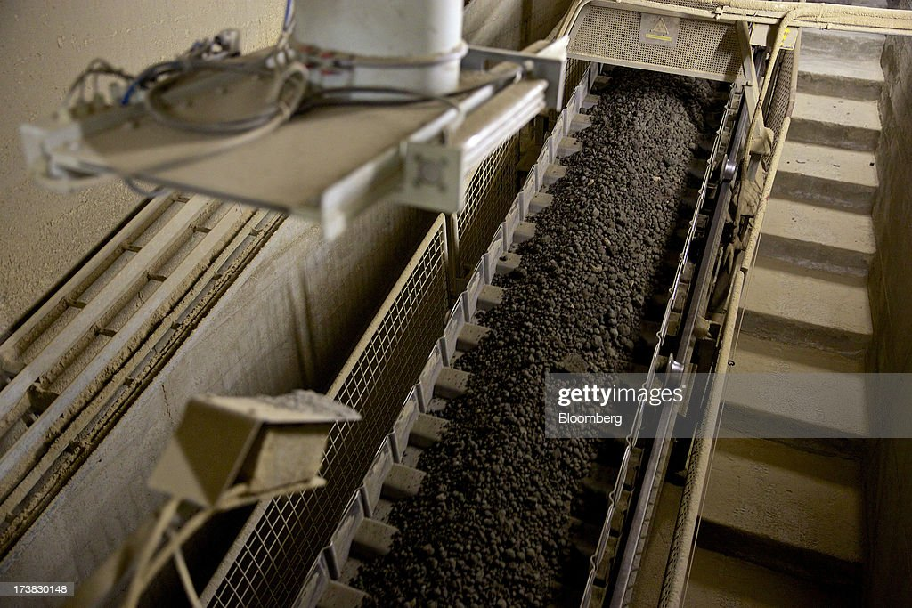 Cement granules travels along a conveyer belt on the production line at Holcim Ltd.'s cement plant in Untervaz, Switzerland, on Wednesday, July, 17, 2013. Holcim Chief Executive Officer Bernard Fontana has cut costs and expanded in emerging regions such as Latin America and Indonesia to counter a construction slump in Europe, caused by the region's economic crisis. Photographer: Gianluca Colla/Bloomberg via Getty Images