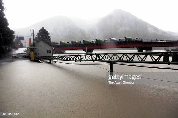 Cement mixer trucks are evacuated on a bridge as a concrete company premises are flooded due to the heavy rain triggered by Thphoon Nangka on July 17...