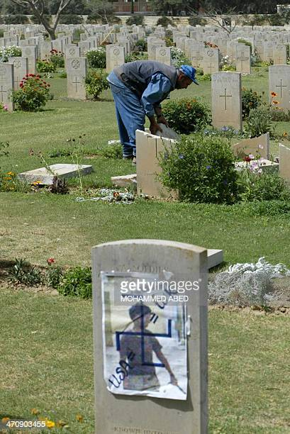 A cemetery guard checks the damage of a broken tomb stone while a picture of an Iraqi prisoner being abused by a US soldier at Abu Ghraib prison in...