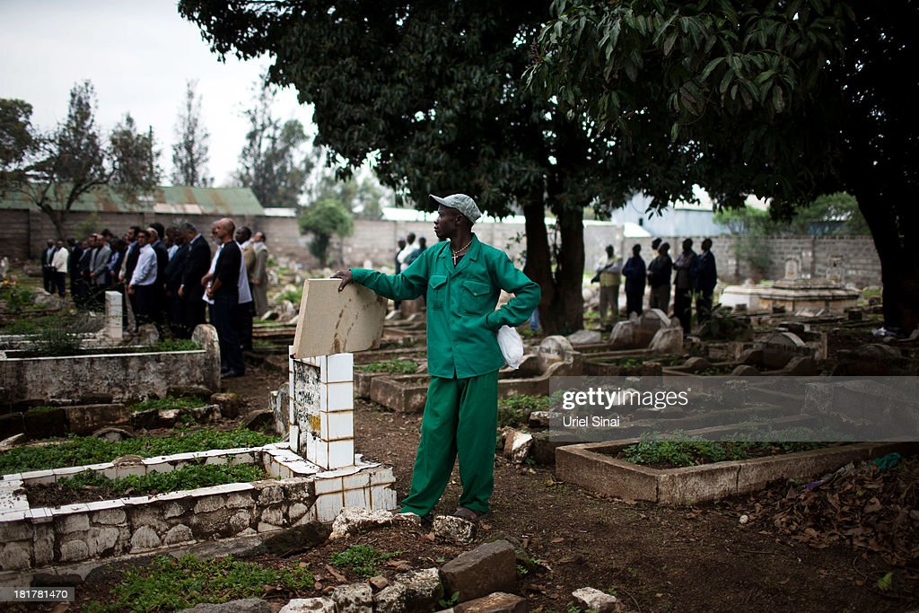 A cemetery worker looks on as friends and relatives mourn during a funeral service for Selima Merali (41) and her daughter Nuriana Merali (15), who were killed in the attack by gunmen at the Westgate Shopping Centre, on September 25, 2013 in Nairobi, Kenya. The country is observing three days of national mourning as security forces begin the task of clearing and securing the Westgate shopping mall following a four-day siege by militants.