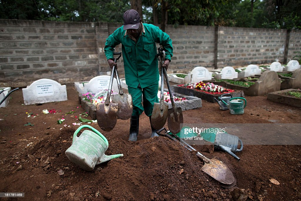 A cemetery worker takes away his tools after the funeral for Selima Merali (41) and her daughter Nuriana Merali (15), who were killed in the attack by gunmen at the Westgate Shopping Centre, on September 25, 2013 in Nairobi, Kenya. The country is observing three days of national mourning as security forces begin the task of clearing and securing the Westgate shopping mall following a four-day siege by militants.
