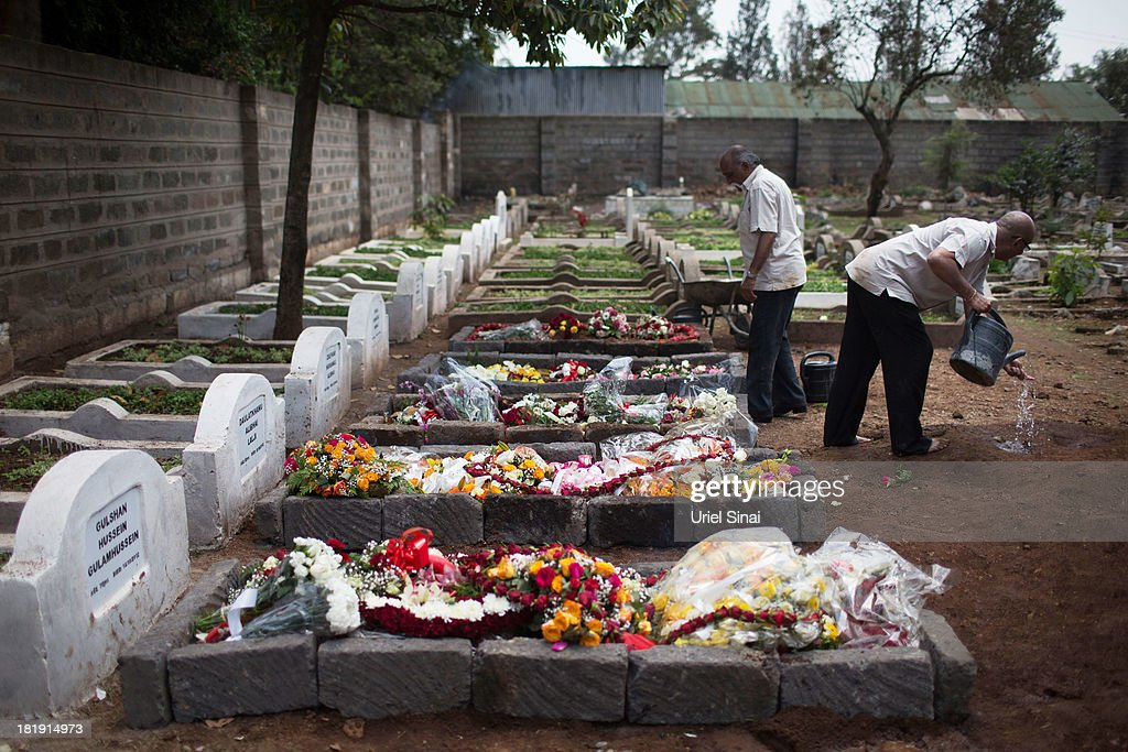 A cemetery worker washes his hands next to five fresh graves after the funeral ceremony of Ruhila Adatia Sood, A Radio Africa television and radio presenter, on September 26, 2013 in Nairobi, Kenya. The country is observing three days of national mourning as security forces begin the task of clearing and securing the Westgate shopping mall following a four-day siege by militants.