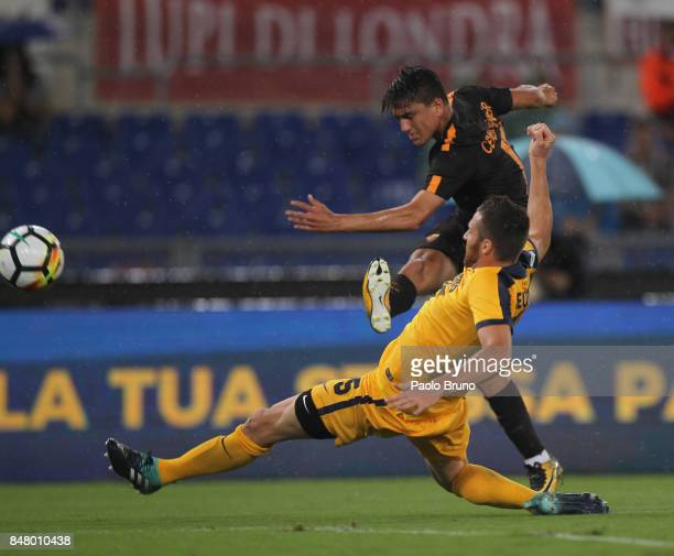 Cengiz Under of AS Roma competes for the ball with Thomas Heurthaux of Hellas Verona FC during the Serie A match between AS Roma and Hellas Verona FC...
