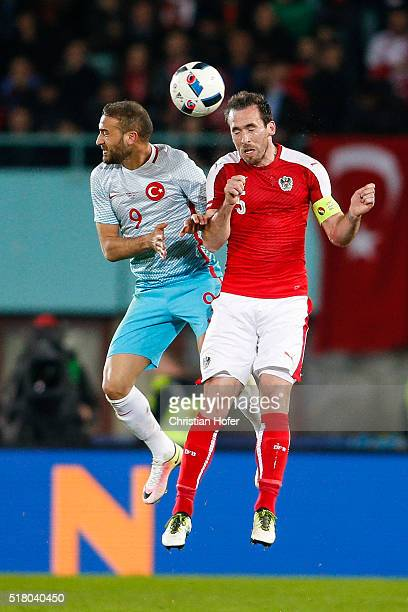 Cenk Tosun of Turkey competes for the ball in the air with Christian Fuchs of Austria during the international friendly match between Austria and...