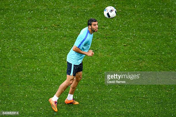 Cenk Tosun of Turkey heads the ball during a training session ahead of their UEFA Euro 2016 Group D match against Spain at Allianz Riviera Stadium on...