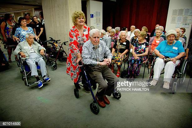 Centenarian Lance Strickland is moved by a carer for a group photograph with Queensland Premier Annastacia Palaszczuk at the Queensland Parliament in...