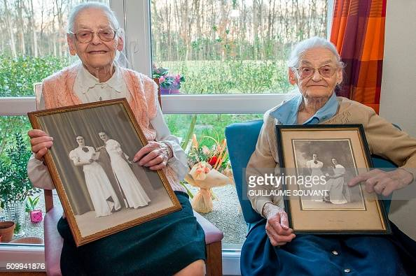 Centenary twins Paulette Olivier and Simone Thiot pose with an old picture of their 20 years inside their room at the retirement home 'Les Bois...