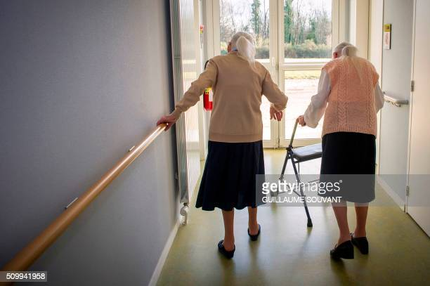 Centenary twins Paulette Olivier and Simone Thiot walk in the corridors at the retirement home 'Les Bois Blancs' on February 11 2016 The twins birth...