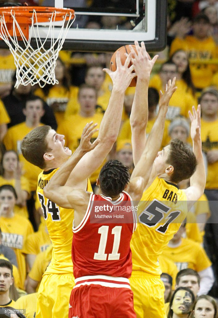 Center Adam Woodbury and forward Nicholas Baer the Iowa Hawkeyes battle for a rebound with guard Jordan Hill the Wisconsin Badgers in the second half...