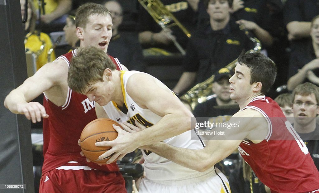 Center Adam Woodbury #34 of the Iowa Hawkeyes battles for a rebound during the first half against forwards Cody Zeller #40 and Will Sheehery #0 of the Indiana Hoosiers on December 31, 2012 at Carver-Hawkeye Arena in Iowa City, Iowa. Indiana won 69-65.