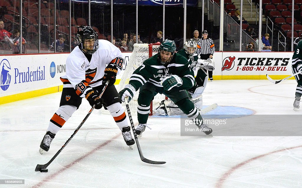 Center Andrew Calof #18 of the Princeton Tigers attempts to get past defenseman Rick Pinkston #7 of the Dartmouth Big Green at Prudential Center on October 25, 2013 in Newark, New Jersey. The Princeton Tigers won 3-2 in overtime.