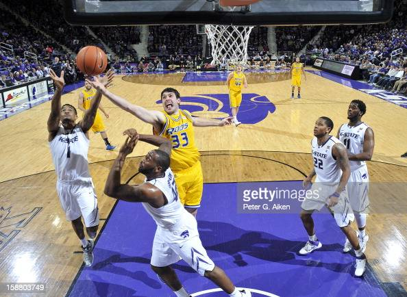 Center Brad Reid of the MissouriKansas City Kangaroos reaches for a rebound against Shane Southwell and Thomas Gipson of the Kansas State Wildcats...