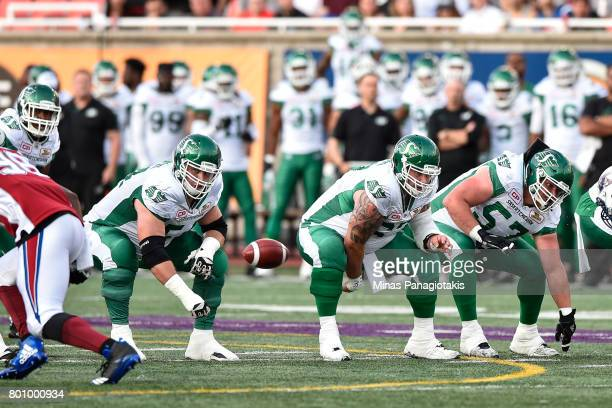 Center Dan Clark of the Saskatchewan Roughriders plays the ball against the Montreal Alouettes during the CFL game at Percival Molson Stadium on June...