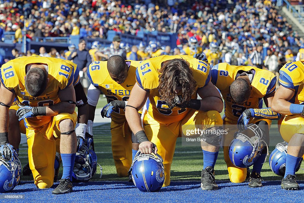 Center David Peterson and tight end Billy Freeman of the San Jose State Spartans kneel down in the endzone before a game against the Fresno State...