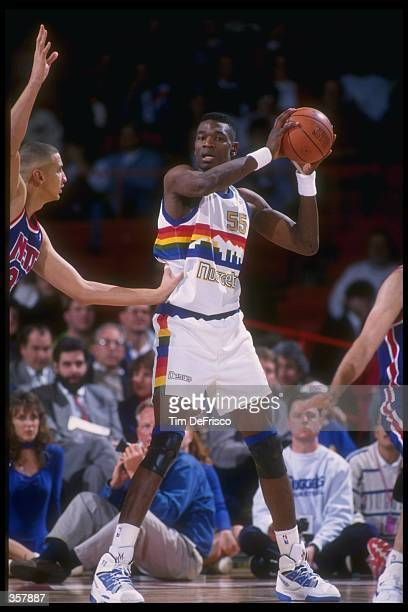 Center Dikembe Mutombo of the Denver Nuggets looks to pass the ball during a game against the New Jersey Nets at McNichols Arena in Denver Colorado