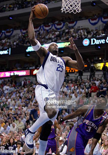 Center Erick Dampier of the Dallas Mavericks goes for the slam dunk against Quentin Richardson of the Phoenix Suns in Game three of the Western...
