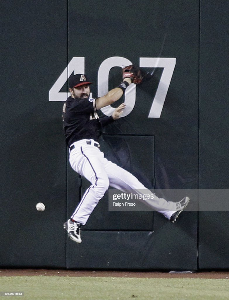 Center Fielder <a gi-track='captionPersonalityLinkClicked' href=/galleries/search?phrase=Adam+Eaton&family=editorial&specificpeople=210898 ng-click='$event.stopPropagation()'>Adam Eaton</a> #6 of the Arizona Diamondbacks has the ball bounce away as he tries to make a play on a double by Todd Helton #17 of the Colorado Rockies during the sixth inning of a MLB game at Chase Field on September 14, 2013 in Phoenix, Arizona.