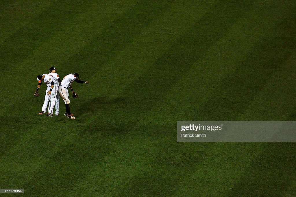 Center fielder Adam Jones #10 of the Baltimore Orioles celebrates with teammates <a gi-track='captionPersonalityLinkClicked' href=/galleries/search?phrase=Nate+McLouth&family=editorial&specificpeople=536572 ng-click='$event.stopPropagation()'>Nate McLouth</a> #9 and <a gi-track='captionPersonalityLinkClicked' href=/galleries/search?phrase=Nick+Markakis&family=editorial&specificpeople=614708 ng-click='$event.stopPropagation()'>Nick Markakis</a> #21 after defeating the Tampa Bay Rays at Oriole Park at Camden Yards on August 21, 2013 in Baltimore, Maryland. The Baltimore Orioles won, 4-2.