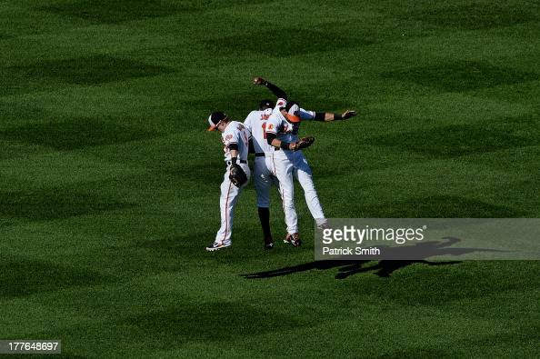 Center fielder Adam Jones of the Baltimore Orioles celebrates with teammates Nate McLouth and Nick Markakis after defeating the Oakland Athletics at...