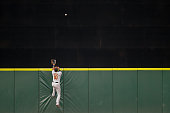 Center fielder Adam Jones of the Baltimore Orioles leaps at the wall for a home run ball off the bat of Nelson Cruz of the Seattle Mariners at Safeco...