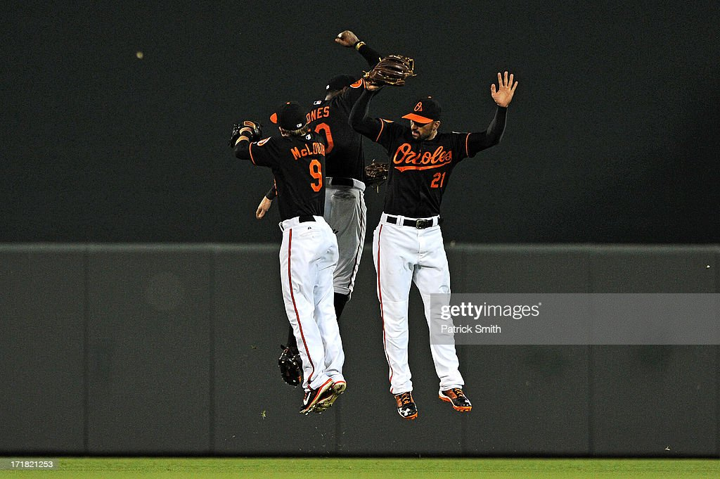 Center fielder Adam Jones #10 of the Baltimore Orioles, left fielder Nate McLouth #9 and right fielder Nick Markakis #21 celebrate after defeating the New York Yankees at Oriole Park at Camden Yards on June 28, 2013 in Baltimore, Maryland. The Baltimore Orioles won, 4-3.