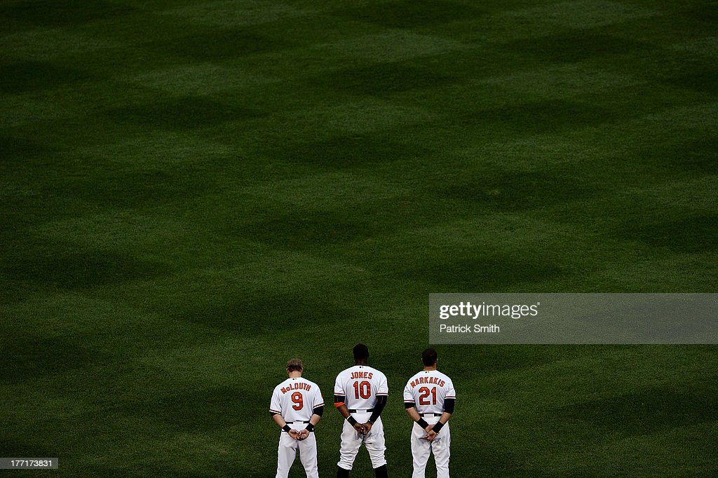 Center fielder Adam Jones #10 of the Baltimore Orioles stands with teammates Nate McLouth #9 and Nick Markakis #21 during the national anthem before playing the Tampa Bay Rays at Oriole Park at Camden Yards on August 21, 2013 in Baltimore, Maryland.