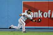 Center fielder Angel Pagan of the San Francisco Giants reaches to catch a line drive hit byJose Peraza of the Los Angeles Dodgers in the fifth inning...
