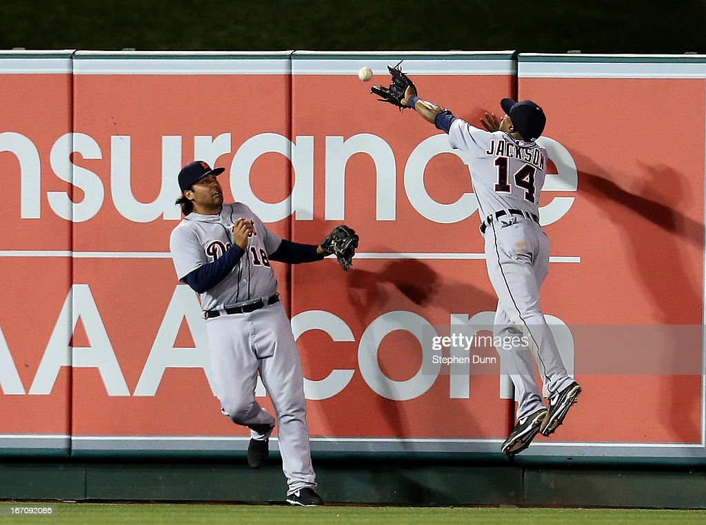 Center fielder <a gi-track='captionPersonalityLinkClicked' href=/galleries/search?phrase=Austin+Jackson&family=editorial&specificpeople=608633 ng-click='$event.stopPropagation()'>Austin Jackson</a> #14 and left fielder Matt Tuiasosopo #18 of the Detroit Tigers can't catch a three run triple hit by Peter Bourjos of the Los Angeles Angels of Anaheim at Angel Stadium of Anaheim on April 19, 2013 in Anaheim, California.