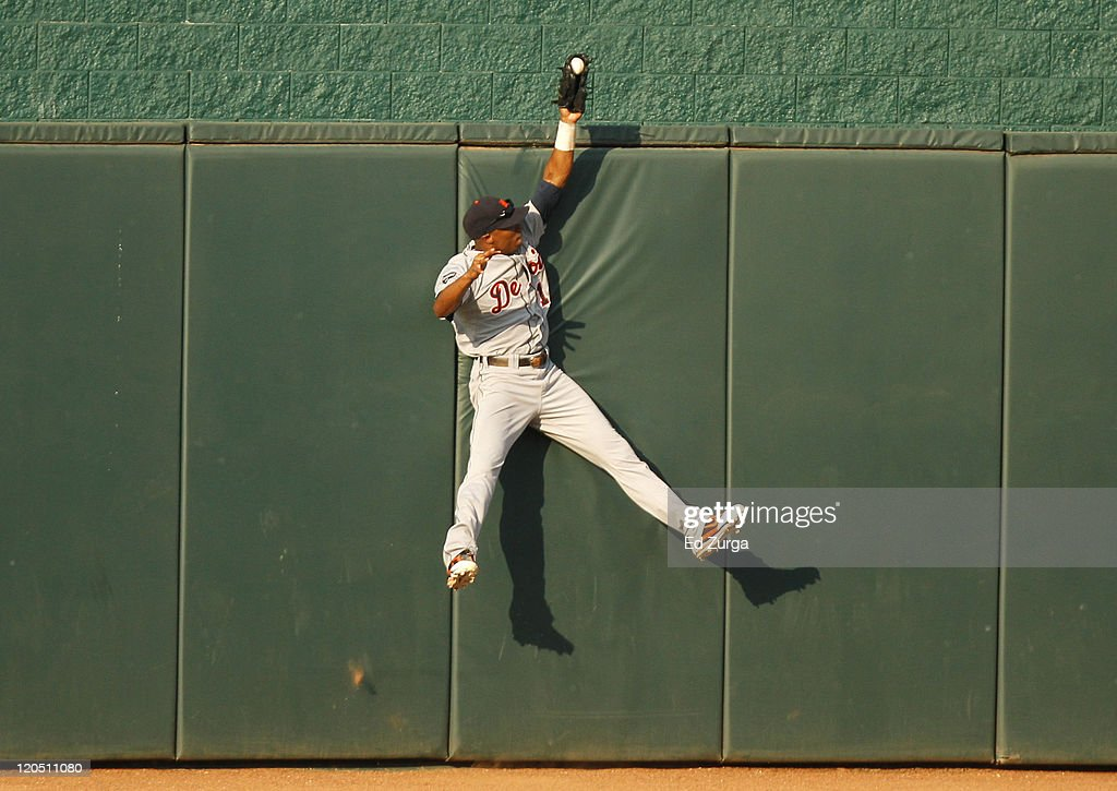 Center fielder <a gi-track='captionPersonalityLinkClicked' href=/galleries/search?phrase=Austin+Jackson&family=editorial&specificpeople=608633 ng-click='$event.stopPropagation()'>Austin Jackson</a> #14 of the Detroit Tigers reaches over the wall as he robs <a gi-track='captionPersonalityLinkClicked' href=/galleries/search?phrase=Alex+Gordon+-+Jugador+de+b%C3%A9isbol&family=editorial&specificpeople=4494252 ng-click='$event.stopPropagation()'>Alex Gordon</a> #4 of the Kansas City Royals of a home run in the first inning at Kauffman Stadium on August 6, 2011 in Kansas City, Missouri.