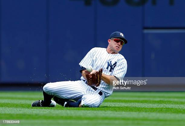 Center fielder Brett Gardner of the New York Yankees can't hold onto the ball after making a diving attempt on a ball hit by Don Kelly of the Detroit...