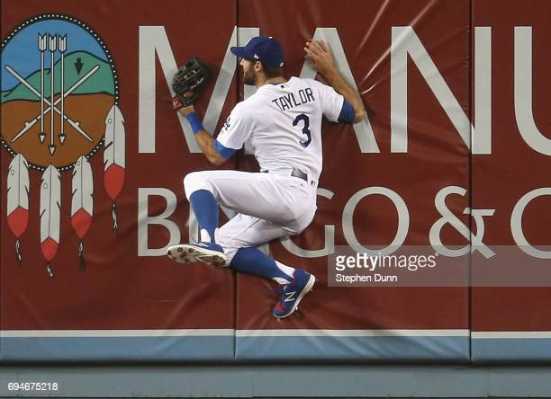 Center fielder Chris Taylor of the Los Angeles Dodgers crashes into the wall after making a leaping catch on a ball hit by Joey Votto of the...
