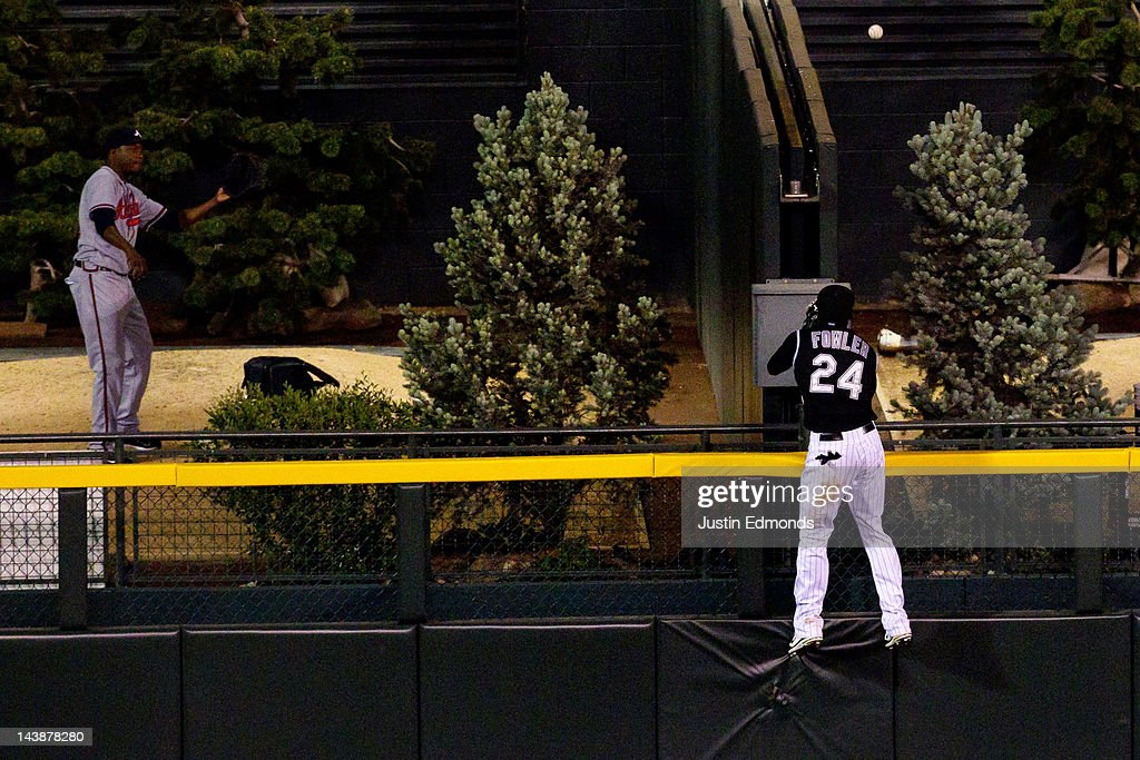 Center fielder Dexter Fowler #24 of the Colorado Rockies climbs the wall to watch the eventual game-winning two-run home run by Eric Hinske #20 of the Atlanta Braves in the top of the 11th inning at Coors Field on May 4, 2012 in Denver, Colorado. The Braves defeated the Rockies 9-8 in 11 innings.